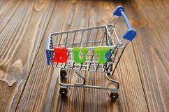 Word `buy` and empty shopping cart on wooden background.  Royalty Free Stock Images