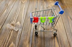 Word `buy` and empty shopping cart on wooden background.  Stock Image