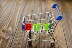 Word `buy` and empty shopping cart on wooden background.  Royalty Free Stock Image