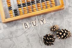 Word BUY laid out of handwritten letters on cardboard squares near old wooden abacus and three cones. On gray cracked concrete royalty free stock photography