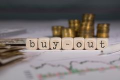 Word BUY-OUT composed of wooden letter. Stacks of coins in the background. Closeup stock photo