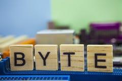Word BYTE op de houten blokken met computers mainboard achtergrond Informatietechnologie achtergrond met mainboard stock afbeelding