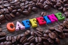 Word cafeïne en koffiebonen Stock Fotografie