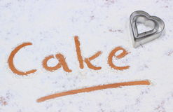 Word cake written in flour and cookie cutters Royalty Free Stock Photos