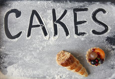 Word CAKES on the flour, together with small cakes Royalty Free Stock Photo