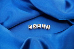 Word Cakes in Food Related Series. Royal blue satin background with rich folds and wrinkles for texture is the word cakes in black and white cube lettering in Royalty Free Stock Images