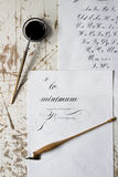 Word Calligraphy written on paper, with calligraphy tools in background. Alphabet Stock Photos