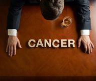 Word Cancer and devastated man composition. Word Cancer made of wooden block letters and devastated middle aged caucasian man in a black suit sitting at the stock image