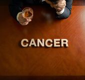 Word Cancer and devastated man composition stock images