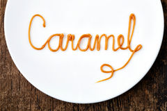 Word Caramel on white plate Stock Images