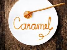 Word Caramel on white plate Royalty Free Stock Photos