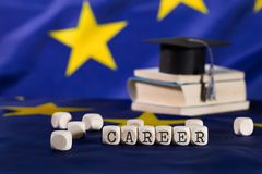 Word CAREER composed of wooden letters. Black graduate hat on EU flag in the background. Closeup royalty free stock photos