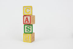 The Word Cash in Wooden Childrens Blocks. Cash - Isolated Text Word In Wooden Childrens Building Blocks with a White Background. The blocks are intentionally Stock Photos