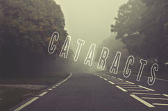 Word cataracts written on foggy, blurred road, danger autumn roa Royalty Free Stock Photography