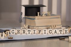 Word CERTIFICATE composed of wooden dices. Black graduate hat and books in the background. Closeup royalty free stock photo