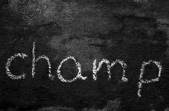 The word champ written with chalk on black stone. Stock Photography