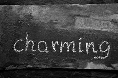 The word CHARMING written with chalk on black stone. Royalty Free Stock Photos