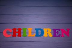 The word children with colorful paper alphabet. On a purple wooden background Stock Photo