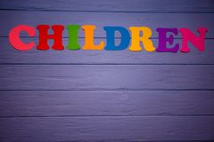 The word children with colorful paper alphabet. On a purple wooden background Stock Image