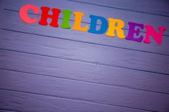 The word children with colorful paper alphabet. On a purple wooden background Stock Photos