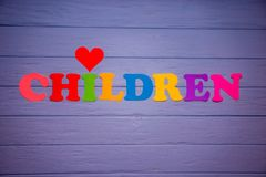 The word children with colorful paper alphabet. On a purple wooden background Royalty Free Stock Photography