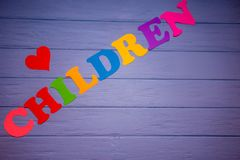The word children with colorful paper alphabet. On a purple wooden background Stock Images