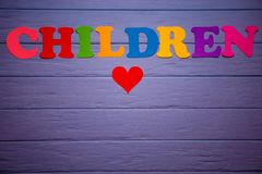 The word children with colorful paper alphabet. On a purple wooden background Stock Photography
