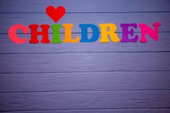 The word children with colorful paper alphabet. On a purple wooden background Royalty Free Stock Images