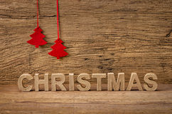 The word christmas in front of a wooden background Royalty Free Stock Photo