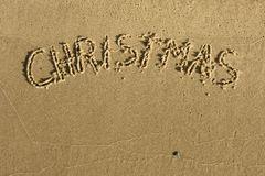 The word Christmas written on sand Stock Image