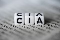 Word CIA formed by wood alphabet blocks on newspaper. Closeup Stock Images