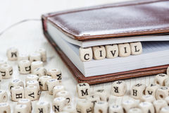 Word CIVIL on old wooden table. Word Civil written on a wooden block in a book. On old white wooden table Stock Photography