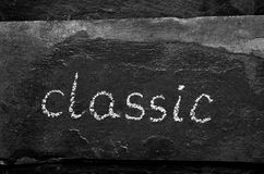 The word classic written with chalk on black stone royalty free stock photos