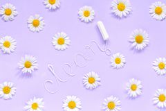 Word CLEAN from white thread hygienic female tampon and chamomiles on lilac background. Word CLEAN from white thread hygienic female tampon surrounded by royalty free stock photos
