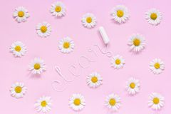 Word CLEAN from white thread hygienic female tampon and chamomiles on pink background. Word CLEAN from white thread hygienic female tampon surrounded by stock photos