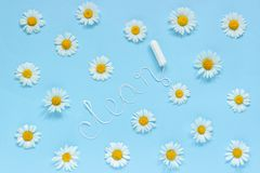 Word CLEAN from white thread hygienic female tampon and chamomiles on blue background. Word CLEAN from white thread hygienic female tampon surrounded by royalty free stock image