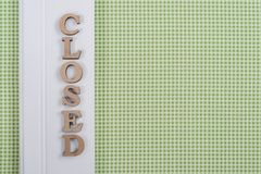 Word closed, abstract wooden letters, green white background stock image