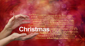 Word Cloud for Christmas. Female hands and a CHRISTMAS word cloud on a sparkling glittery red bokeh background Stock Photos