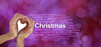Word Cloud for LOVE Christmas. Female hands making a heart shape beside a CHRISTMAS word cloud on a magenta red bokeh background stock photos