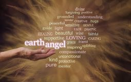 Word Cloud For your Earth Angel. In warm brown tones, a female open hand with floating glowing words EARTH ANGEL and a relevant word cloud with wispy feathers in royalty free stock photo