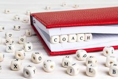Word Coach written in wooden blocks in red notebook on white woo. Den table. Wooden abc stock image