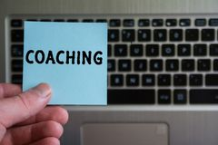 Word COACHING on sticky note. Hold in hand on laptop keyboard background royalty free stock image