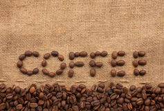 The word coffee. Made from coffee beans on sackcloth next to coffee beans Royalty Free Stock Photo