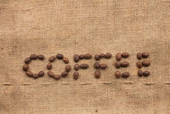 The word coffee. Made from coffee beans on sackcloth next to coffee beans Royalty Free Stock Photos