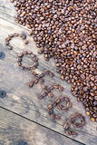 The word coffee beans laid out the wood table. Royalty Free Stock Photos