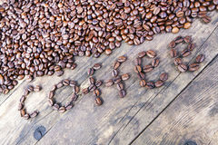 The word coffee beans laid out the wood table. Royalty Free Stock Images