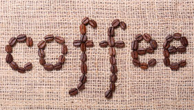 The word coffee made from coffee beans on burlap Stock Photos