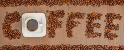 The word Coffee spelled with hundreds of coffee beans and one cu Stock Image