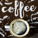 The word coffee is written on ground coffee. A cup of fresh hot coffee with foam next to the word `coffee` written on the ground coffee Royalty Free Stock Photography