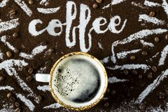 The word coffee is written on ground coffee. A cup of fresh hot coffee with foam next to the word `coffee` written on the ground coffee Stock Image